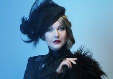 De elegante vrouw op middelbare leeftijd in een zwarte hoed met een sluier en een luxe kleden zich stock afbeelding