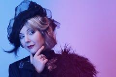 De elegante vrouw op middelbare leeftijd in een zwarte hoed met een sluier en een luxe kleden zich royalty-vrije stock fotografie