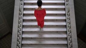 De elegante vrouw in rode lange kleding op hoge hielen beklimt een grote trap en kijkt op camera stock footage