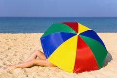 De elegante vrouwen` s benen kijken uit van onder de kleurrijke paraplu Stock Afbeelding