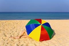 De elegante vrouwen` s benen kijken uit van onder de kleurrijke paraplu Stock Afbeeldingen