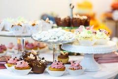 De elegante zoete lijst met cupcakes, cake knalt en suikergoed op diner stock foto