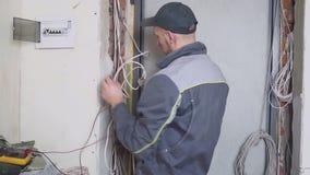 De elektricien op het werk meet de elektrische stroom stock footage
