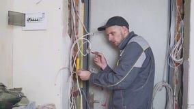 De elektricien op het werk meet de elektrische stroom stock videobeelden