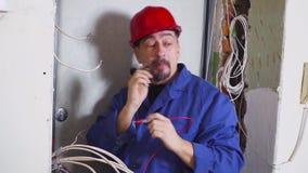 De elektricien op het werk meet de elektrische stroom stock video