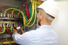De elektricien op het werk meet voltage in industriële distributie fuseboard stock fotografie