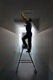 De elektricien op trapladder installeert verlichting aan het plafond Royalty-vrije Stock Afbeelding