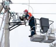 De elektricien verbindt de draden met de lijnisolator Stock Afbeeldingen