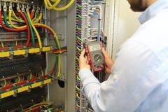 De elektricien werkt in de elektrozekeringkast van de kabelsdistributie met multimeter stock afbeeldingen