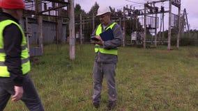 De elektricieningenieur geeft de taak om het gras in hulpkantoor te snijden stock video