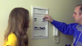 De elektricienman verklaart voor de cliënt van de huisvrouwenvrouw hoe te om stroomonderbrekerdoos te gebruiken stock footage