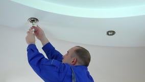 De elektricienmens installeert of vervangt halogeen lichte lamp in plafond stock footage
