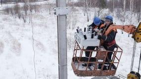 De elektriciens heffen omhoog in het dek van de vrachtwagenkraan op de winterdag op stock footage