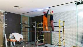 De elektriciens installeren geleide lampen op ruimteplafond timelapse stock footage