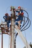 De elektriciens lossen op machtslijnen problemen op Royalty-vrije Stock Afbeeldingen