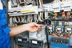 De elektricienwerken met elektrisch metermeetapparaat in zekeringkast Stock Foto's