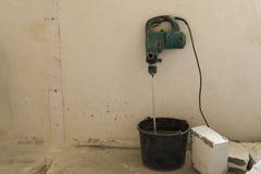 De elektrische boor in de emmer met cement voor gas blokkeert het leggen royalty-vrije stock foto's