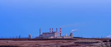 De elektrische centralebouw met rokende pijpen en het gloeien lichten in Th stock afbeeldingen
