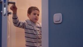 De elektrische energie - besparingen, de inschakelen van de kindjongen steekt en gaat toilet aan in stock videobeelden
