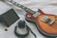 De elektrische gitaar is op een witte deken Stock Afbeelding