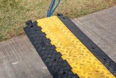 De elektrische kabel is protectd binnen grunged langs plastic verkeersdrempel Stock Foto