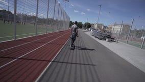 De elektrische Longboard-mens in sweatshirt en de hoed berijden op rood sportstadion met speelplaats stock footage