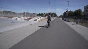 De elektrische Longboard-mens in sweatshirt en de hoed berijden op rood sportstadion met speelplaats stock videobeelden