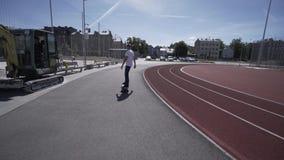 De elektrische Longboard-mens in witte t-shirt en de hoed berijden op rood sportstadion met speelplaats stock video