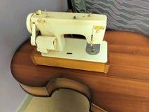 De elektrische naaimachine van witte kleurenkosten op een bruine houten lijst van de oude gebroken contrabas van een muzikaal ins stock afbeeldingen