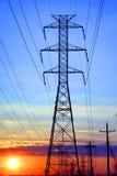 De elektrische Toren van de Transmissie van de Hoogspanning bij Zonsondergang Royalty-vrije Stock Afbeeldingen