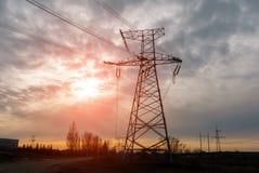 De elektrische toren van de silhouethoogspanning op zonsondergangtijd en hemel op de achtergrond van de zonsondergangtijd Stock Foto's