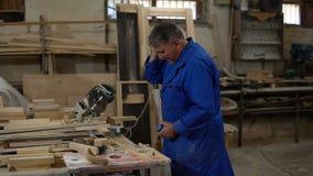 De elektrische zaag voor het zagen van raad, arbeider zaagt een houten raad in de workshop stock footage