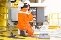De elektro en instrumentenarbeider inspecteert en controlerend voltage en stroom van elektrisch systeem bij olie en gasplatform p royalty-vrije stock afbeeldingen