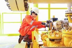 De elektro en Instrumententechnicus vervangt solenoïdeklep van sluitingsklep bij olie en gasbron ver platform royalty-vrije stock afbeeldingen