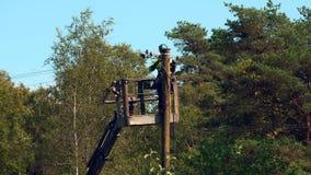 De elektroarbeider herstelt een probleem aangaande de machtslijn, een deel 3 van 3 stock footage