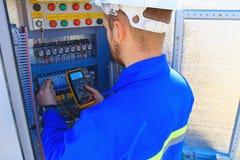 De elektroingenieur met een multimeter voert het aanpassingswerk in het vage controlekabinet uit stock afbeeldingen