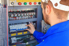 De elektroingenieur voert omschakeling van industrieel materiaal op een vage achtergrond van het controlekabinet uit Royalty-vrije Stock Fotografie