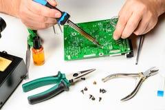 De elektronikatechnicus vervangt het non-working element van het elektronische apparaat met een soldeerbout De handen van stock fotografie