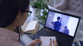 De elektronische opleiding, studente in oogglazen met pen schrijft in blocnote tijdens het letten op video op een notitieboekje stock videobeelden