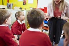 De Elementaire Scholieren van leraarsreading story to Stock Foto's