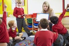 De Elementaire Scholieren van leraarsteaching spelling to Stock Foto's