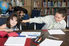 De elementaire student krijgt haar haar dat in bibliotheek wordt getrokken stock fotografie