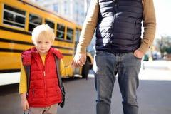 De elementaire studentengreep overhandigt zijn vader dichtbij gele schoolbus op achtergrond stock fotografie