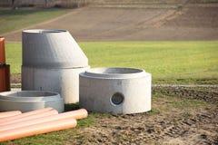 De elementen van betonconstructies voor de regeling van rioleringssystemen liggen op het groene gras in de stralen van de zon De  royalty-vrije stock fotografie