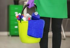De emmer van de vrouwenholding met het schoonmaken van producten stock foto's