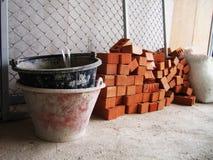 De emmers en de rode bakstenen treffen voor bouw voorbereidingen Stock Afbeeldingen
