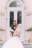 De emotionele foto van de glimlachende jonggehuwden terwijl status op de treden van het Oostenrijkse gebouw stock foto's