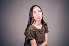 De emotionele jonge mooie vrouw toont tong en bekijkt camera royalty-vrije stock fotografie