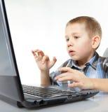 De emotionele jongen van de computerverslaving met laptop Stock Afbeeldingen