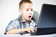 De emotionele jongen van de computerverslaving met laptop Stock Foto's